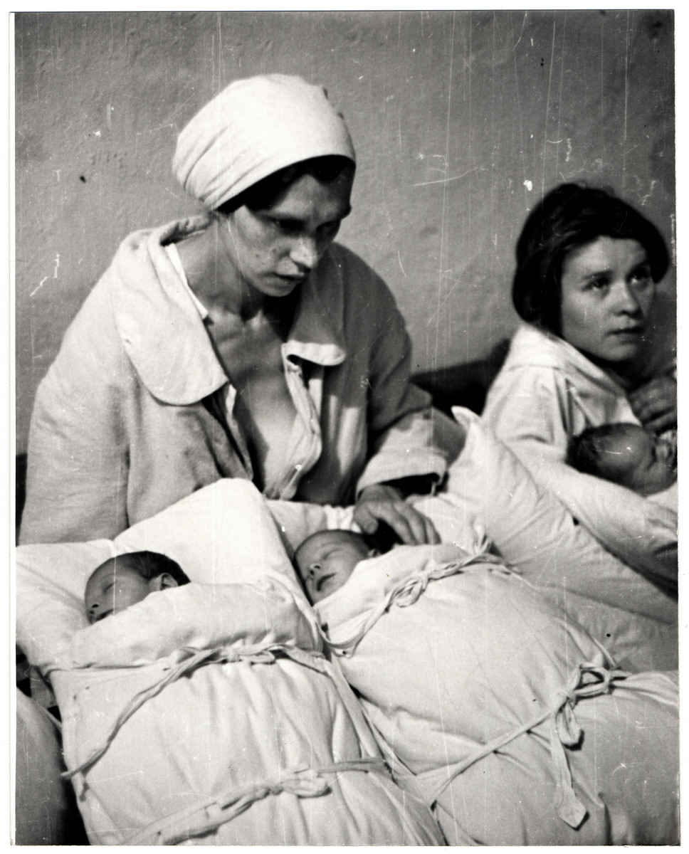 Two Polish mothers pose with their newborn infants during the siege of Warsaw.