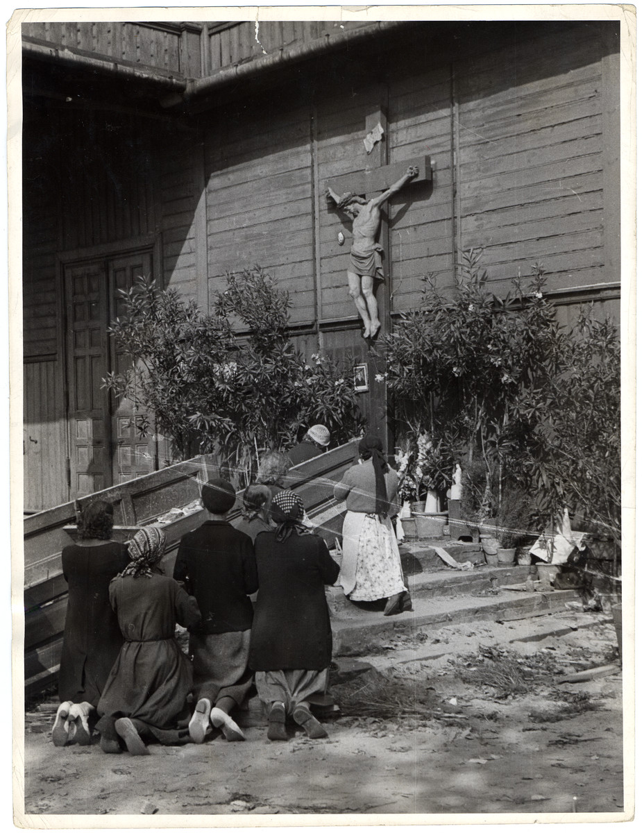 "A group of Polish women pray on their knees before a large crucifix hanging outside an old wooden church that had been bombed by German aircraft a day earlier.  In the words of photographer Julien Bryan, ""The entire right wing of the building had been blown away, and where this section had been was an enormous crater, thirty feet across and fifteen feet deep.  The rest of the building was still standing.  A young Catholic priest with a serene face showed us about.  Luckily, he said, they had heard the alarm for an air attack and he managed to get all his parishioners out of the church before the bomb struck.""  [Source: Bryan, Julien.  ""Warsaw 1939 Siege, 1959 Warsaw Revisited.""  Warsaw, Polonia, 1959, p. 22]"