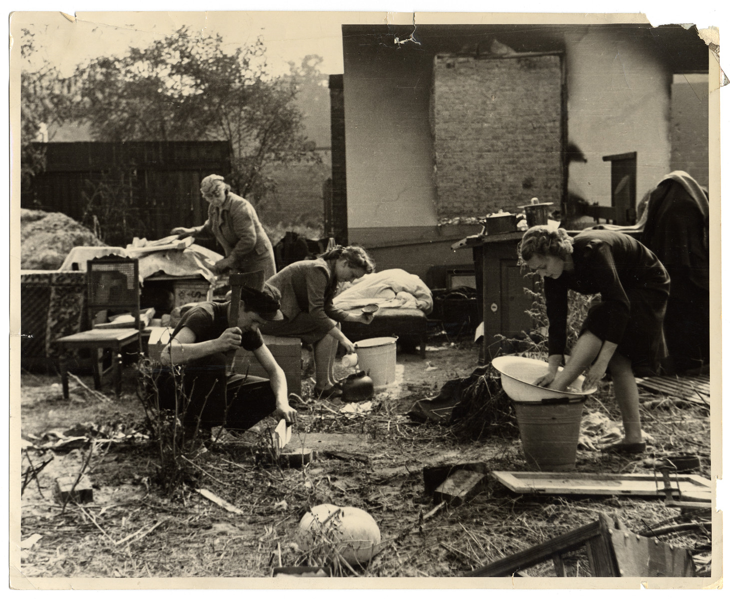 A Polish family performs their daily chores amidst the remnants of their household furnishings that they have reassembled outside the charred ruins of their home in Warsaw.