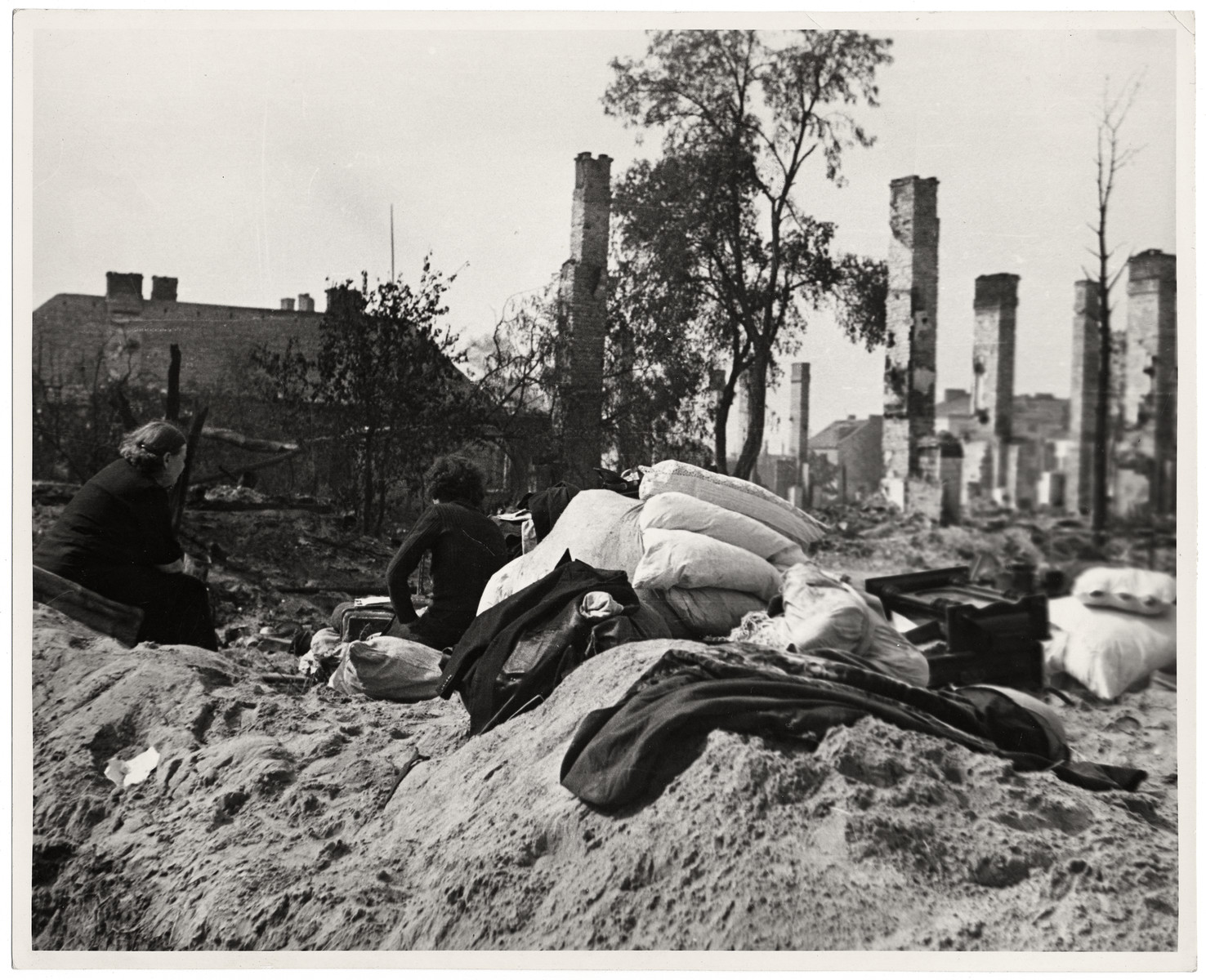 Two women sit amidst the ruins of their homes in Warsaw with a pile of bedding they were able to save.