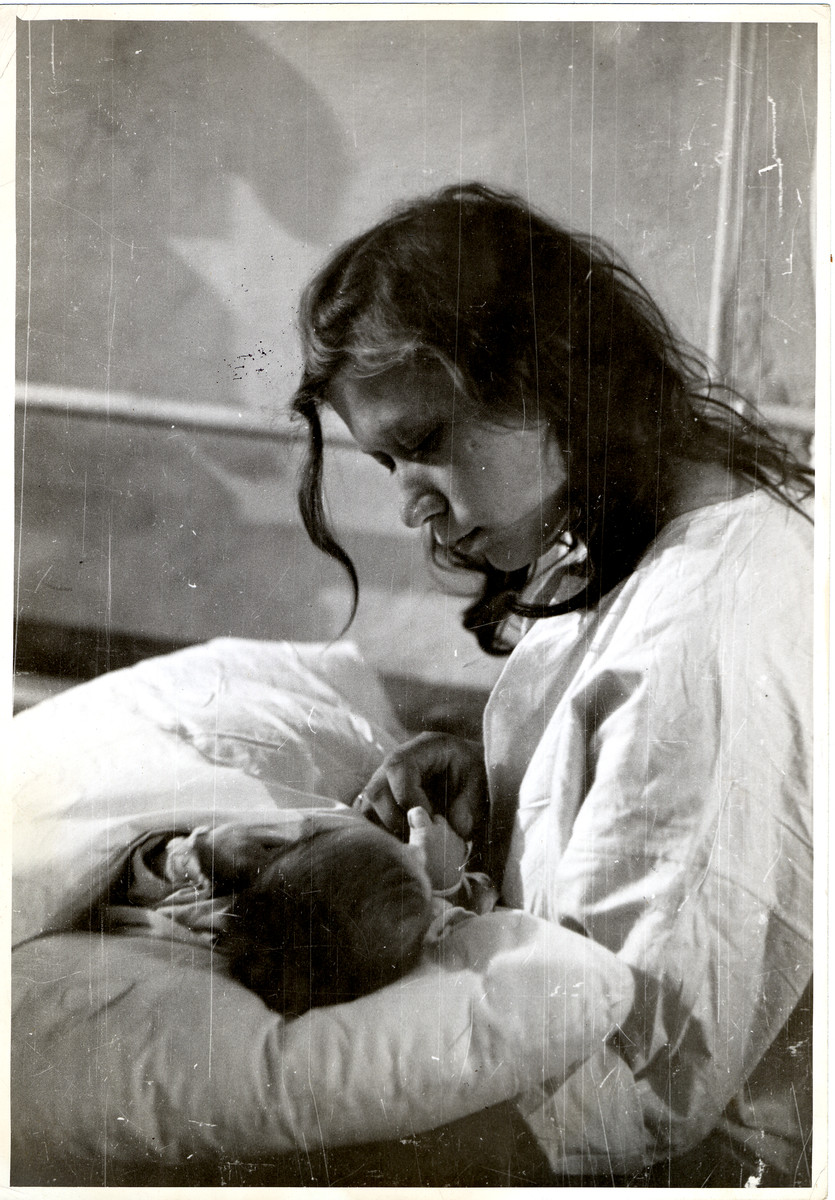 A Polish woman tends her newborn infant in besieged Warsaw.