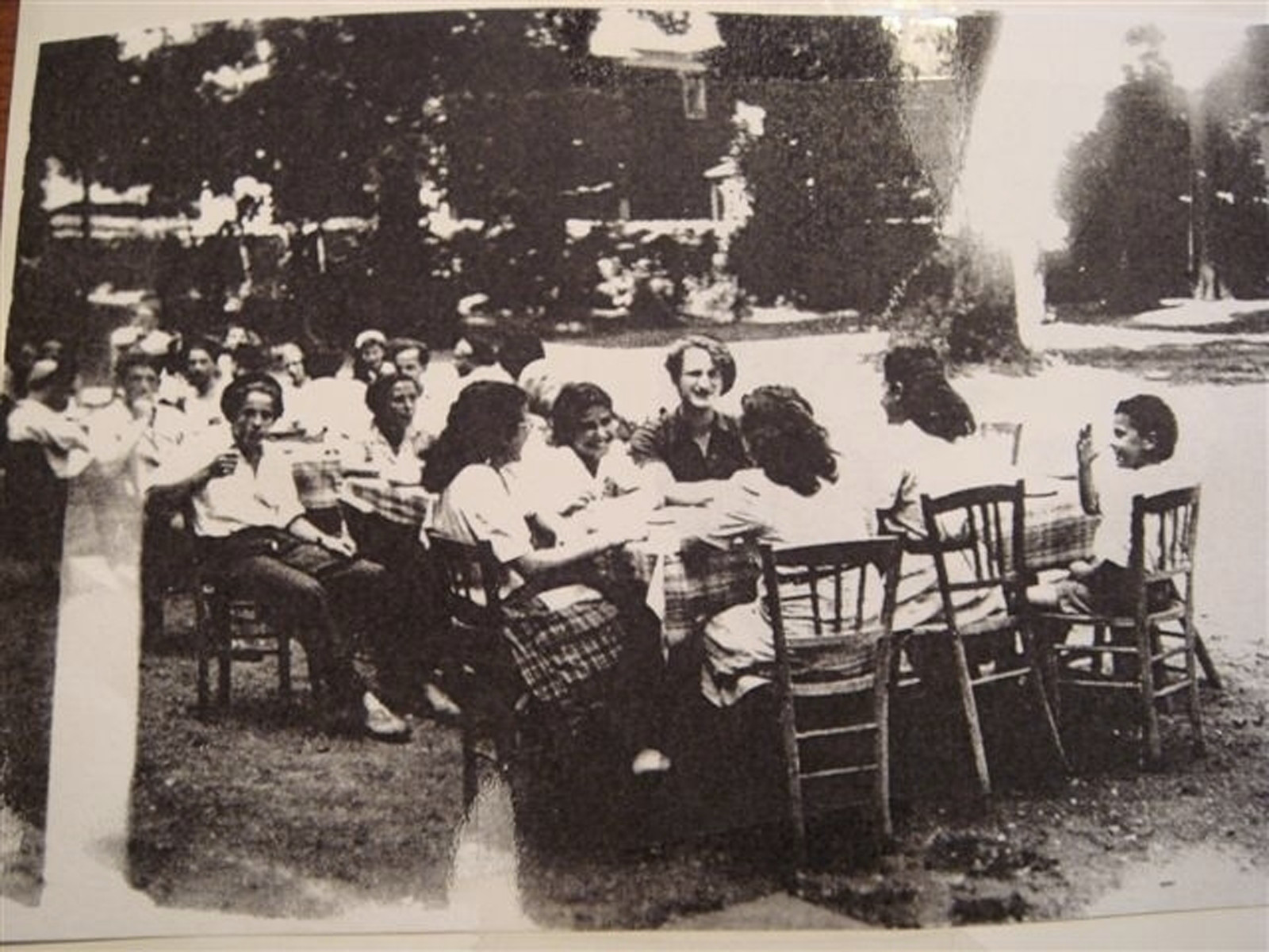 Teenagers from the Versailles children's home sit outside around tables.  Among those pictured is Mathilde (Tilly) Goldschmidt.