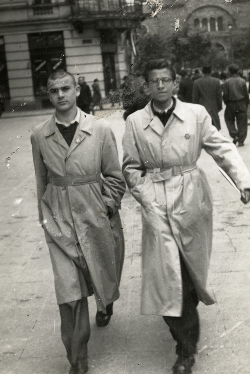 Josef Dekalo and Marcel Confino walk down a street in Sofia wearing Jewish badges.