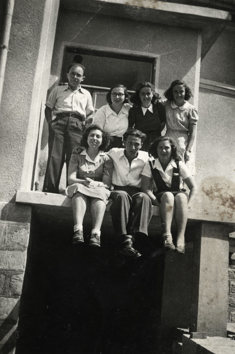 A group of young Jewish Bulgarians pose on the ledge of a building.    Dora Levy is pictured on the bottom left.