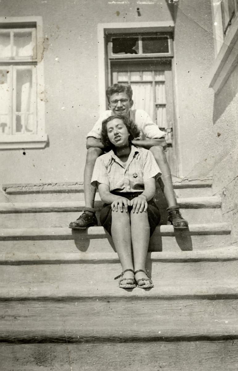 Marcel Confino and Dora Levy sit on the steps of a building in Razgrad wearing Jewish badges.
