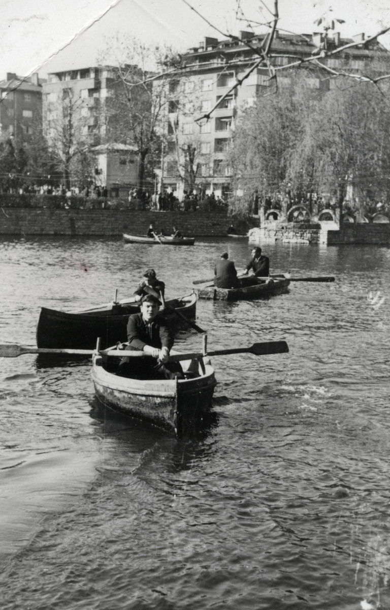 Joseph Dekalo rows a boat on a lake in Sofia wearing his school uniform.