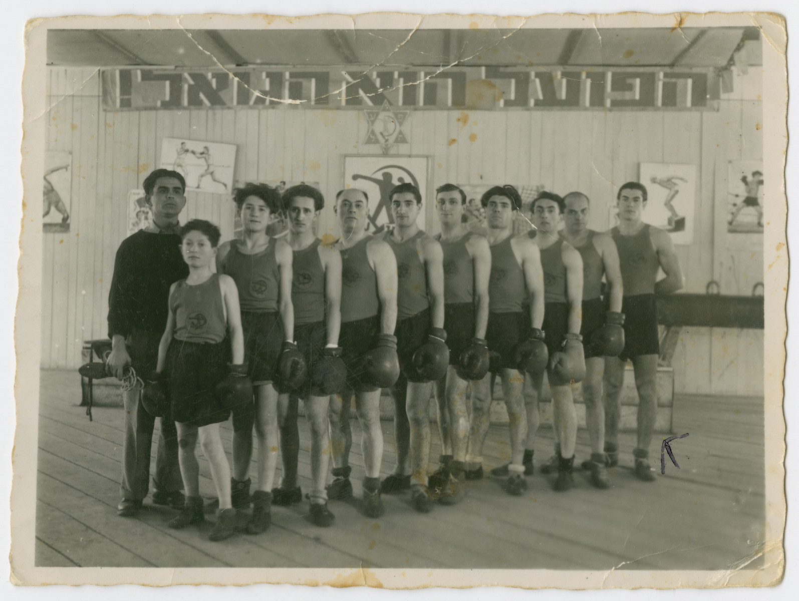 "Group portrait of the members of the boxing club in Feldafing.  Richard Gutnner is at the end of the row.  The sign in Hebrew reads ""HaPoel Hu HaGoel"" [The worker is the redeemer.]"
