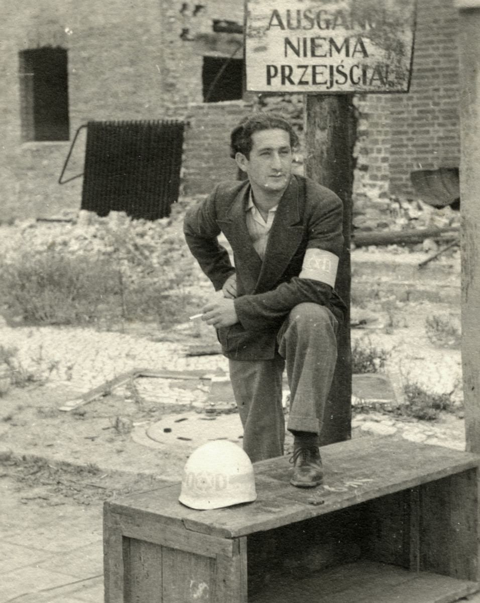 Nathan Schwarzfeld, a Jewish policeman in the Tempelhof displaced person camp, poses wearing an armband with his police helmet next to him.