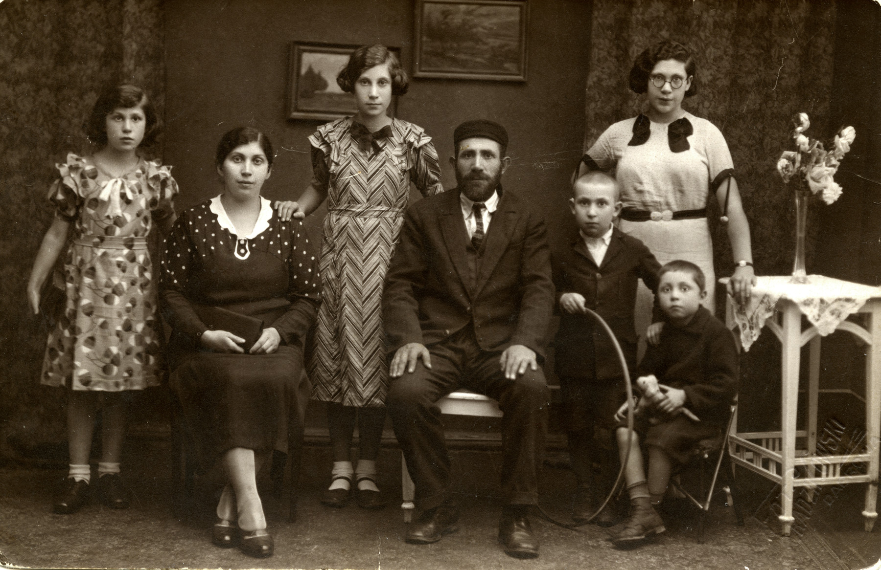 Studio portrait of the Welner family from Dabrowa Gornicza.   From let to right; Ruzia Welner, Pesla, Rywka (donor's mother), Mordechai, Shimon, Shimshon, Hannah (standing behind). The photograph had been sent to Mordechai's brother, Getzel Welner, in America.