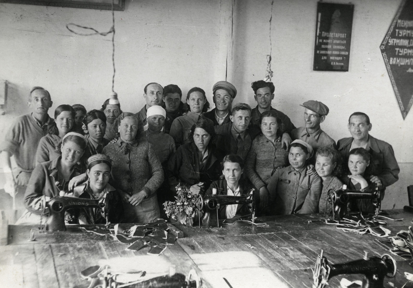 Workers at the Sparta shoe factory pose with their sewing machines.  Jonas Markowicz is standing on the right,