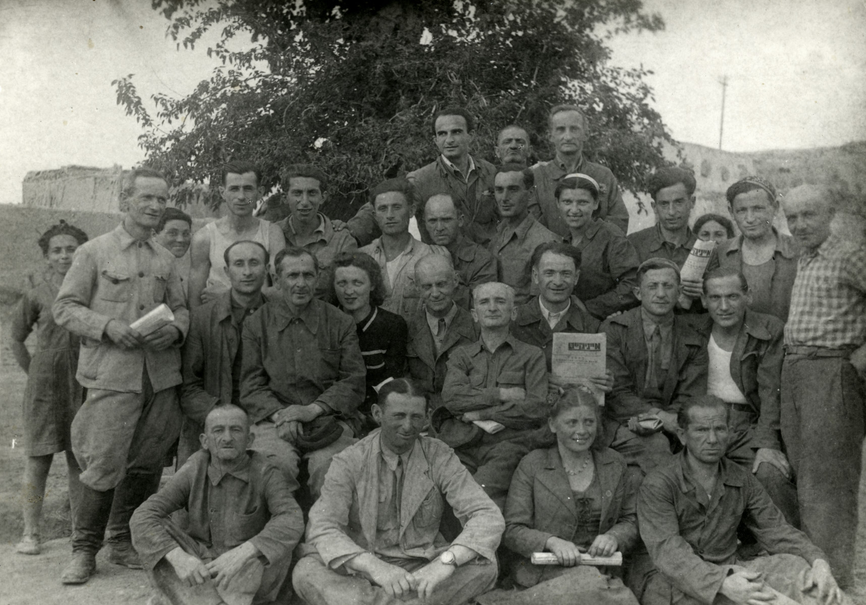 Group photograph iof Jewish refugees in Bukhara, some holding Yiddish newspapers.  Jonas Markowicz and Abraham Levine are sitting on the right of the second row.