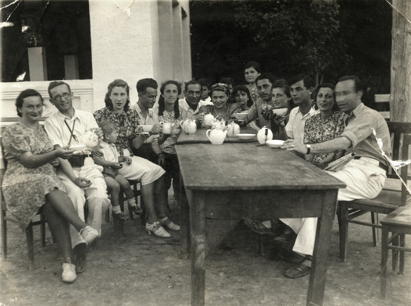 A group of Polish Jewish refugees and local friends enjoys a cup of tea at Chai Hana.   From left, Lonya Amster, Israel Greenbaum, Rywka (donor's mother) hugging Benjamin, Mr. and Mrs. Goldberg, Jonas Markowicz  (donor's father) and other Uzbeki and Jewish refugee friends.