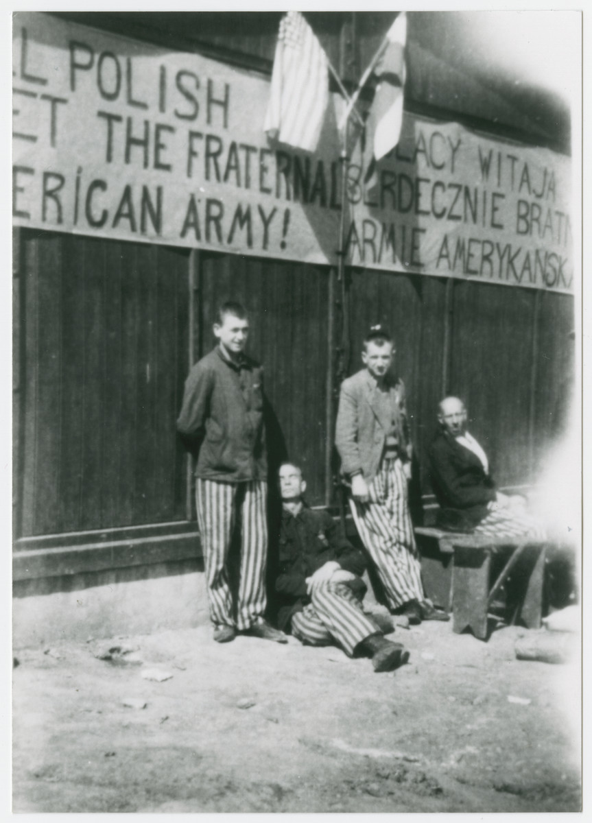 "Polish prisoners relax underneath a banner greeting their American liberators.  The original caption reads: ""Side of the Polish barracks with the poor worn out and very weak P.W.s -- They stood outdoors weather permitting, as much as they could, to escape the foul conditions inside of the barracks.  Inside the barracks were 5 or 6 wooden shelves from one end to the other, Each shelf was partitioned off into 6' spaces.  You lived and died in those spaces.  If the guy above you had dysentery (diarreha) tough on you!"""
