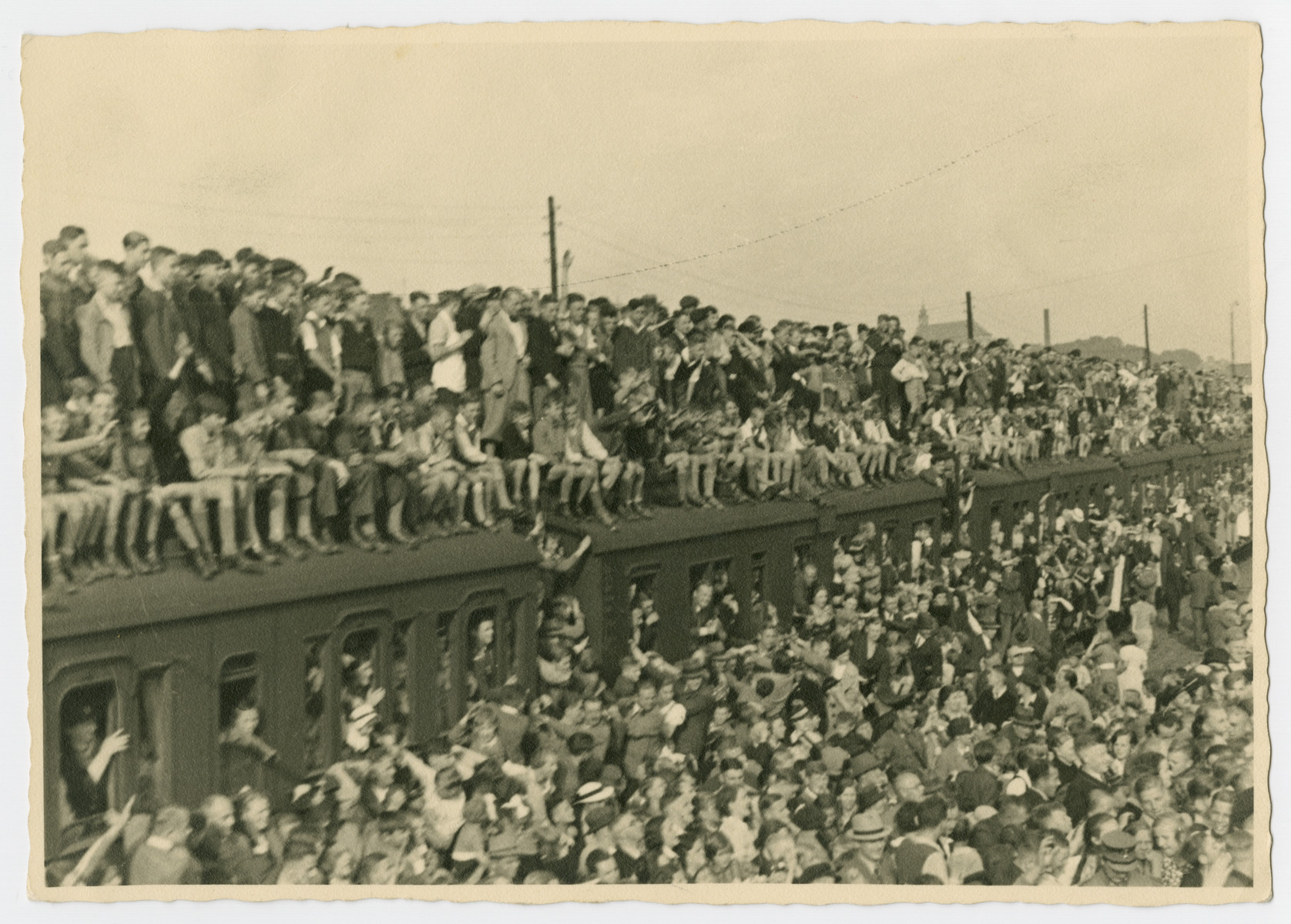 Crowds of people gather in front of and on top of a train to participate in a May Day Nazi party parade.