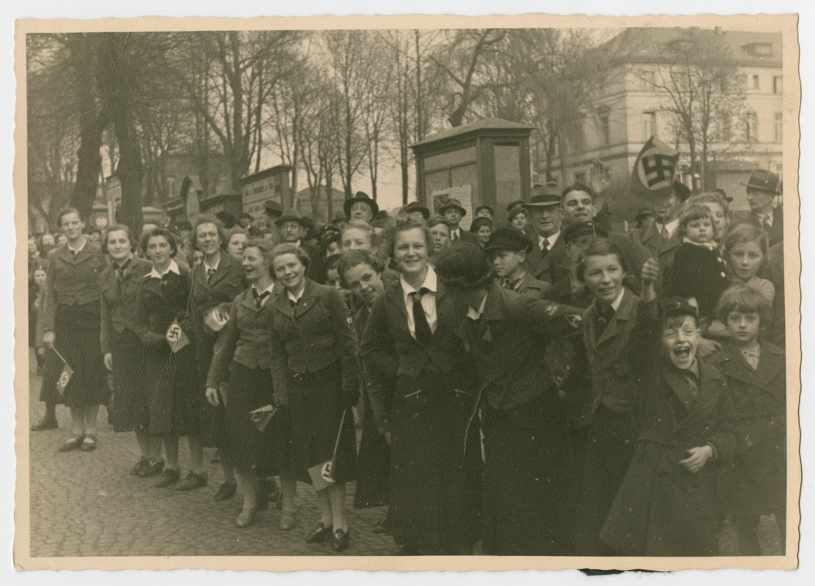 Children line a street to cheer on a Nazi May Day parade.