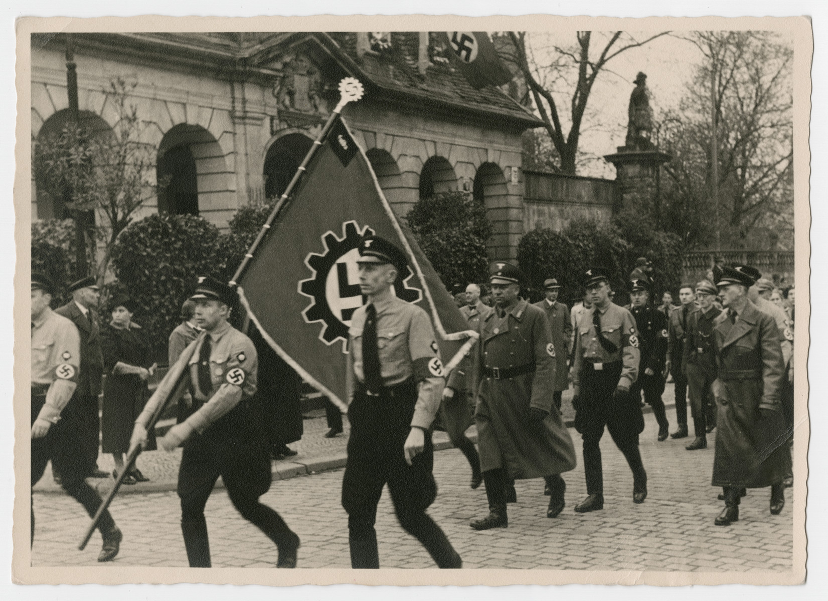 Members off the German Labor Front march down a street in Fulda carrying the Cog Wheel Swastika during a May Day Nazi party parade.
