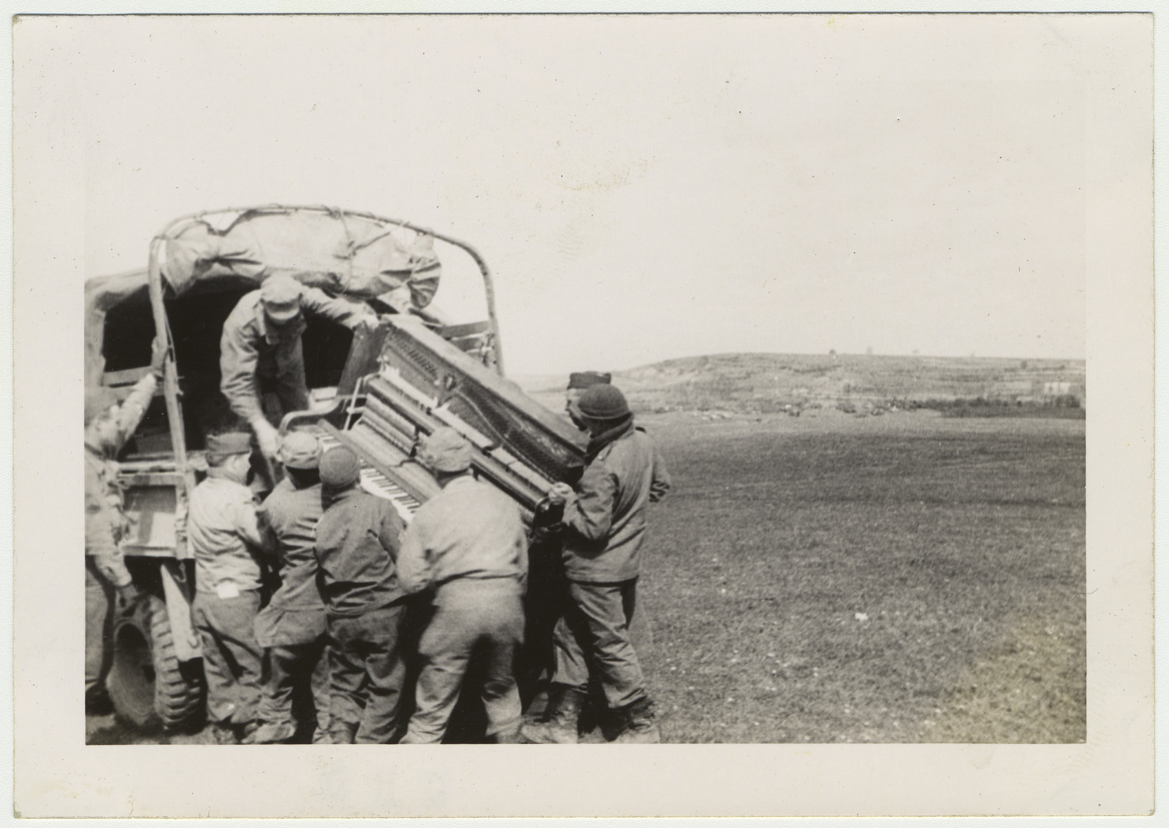 """American soldiers load a piano onto a truck.  Original caption:  Loading the Loot-- a """"liberated plane"""""""