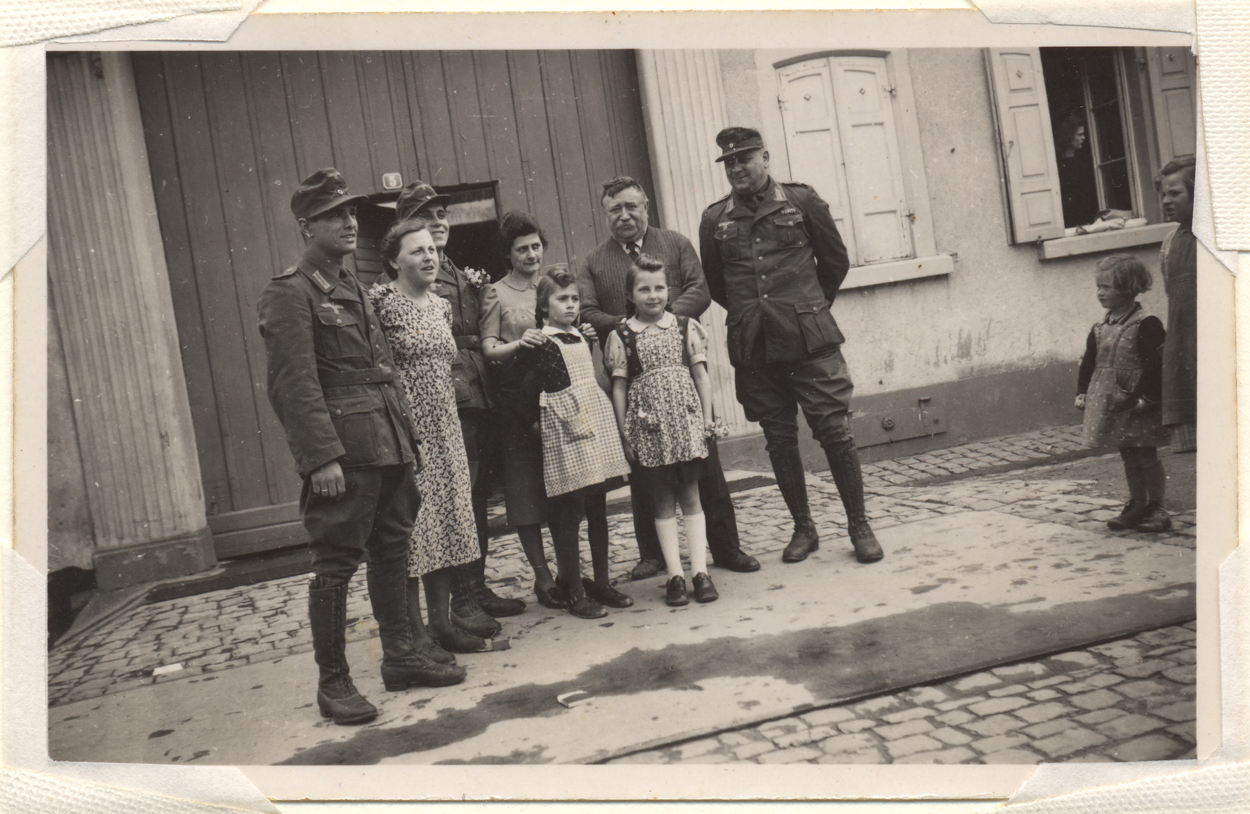 A group of civilians poses next to members of the German army.