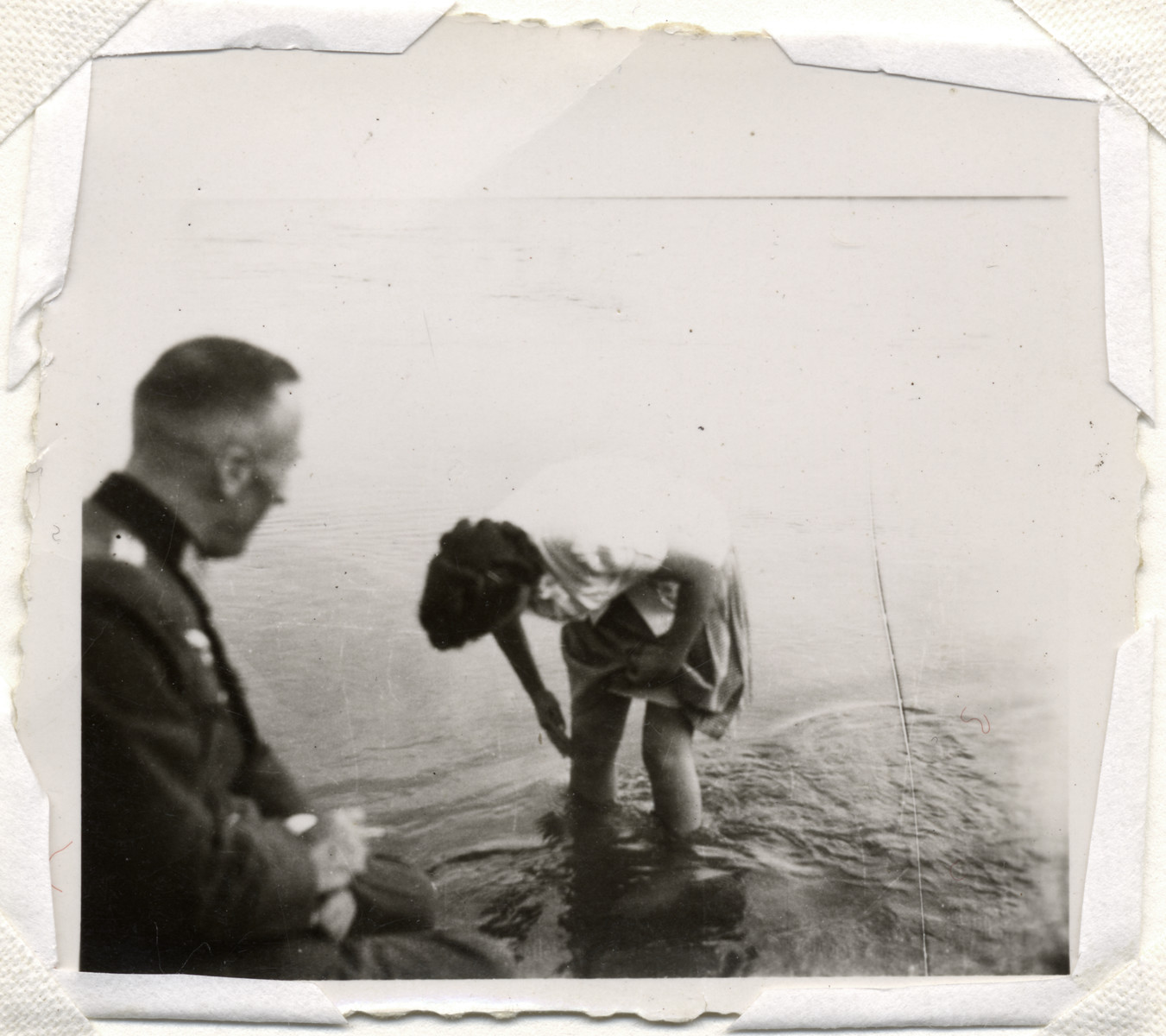 A German soldier observes a woman wading in a lake.