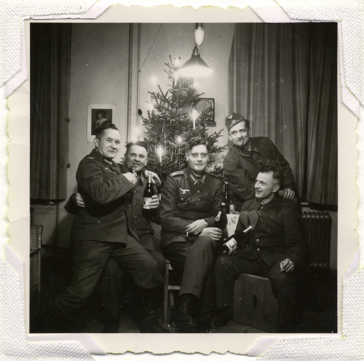 German soldiers pose in front of a Christmas tree.