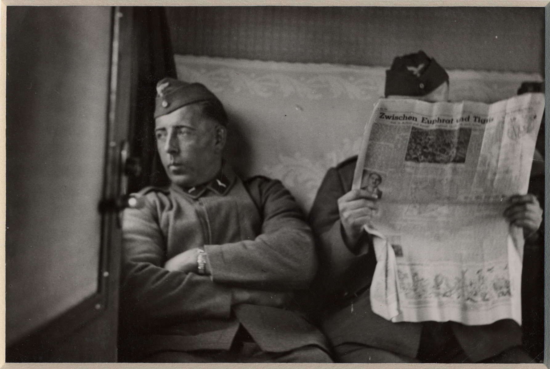 "Two German men sit in a train car; one is reading a newspaper.  The back page is a story entitled ""Between the Tigres and the Euphrates""."