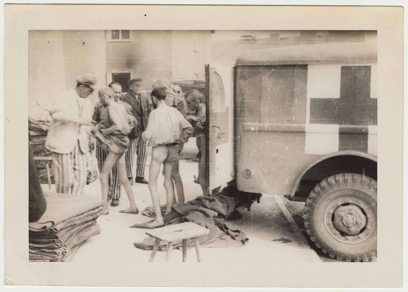 Concentration camp survivors stand next to an ambulance.