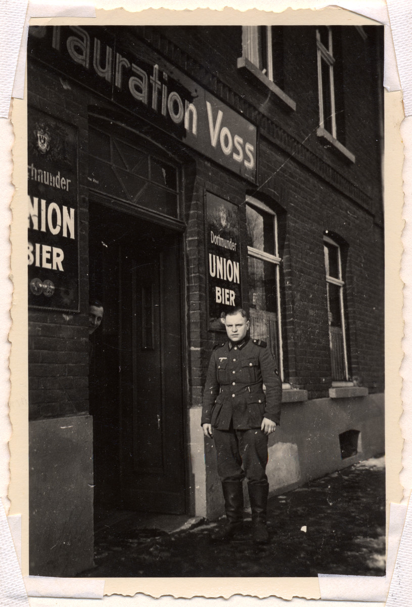 A German soldier stands outside a building with signs advertising brands of beer.