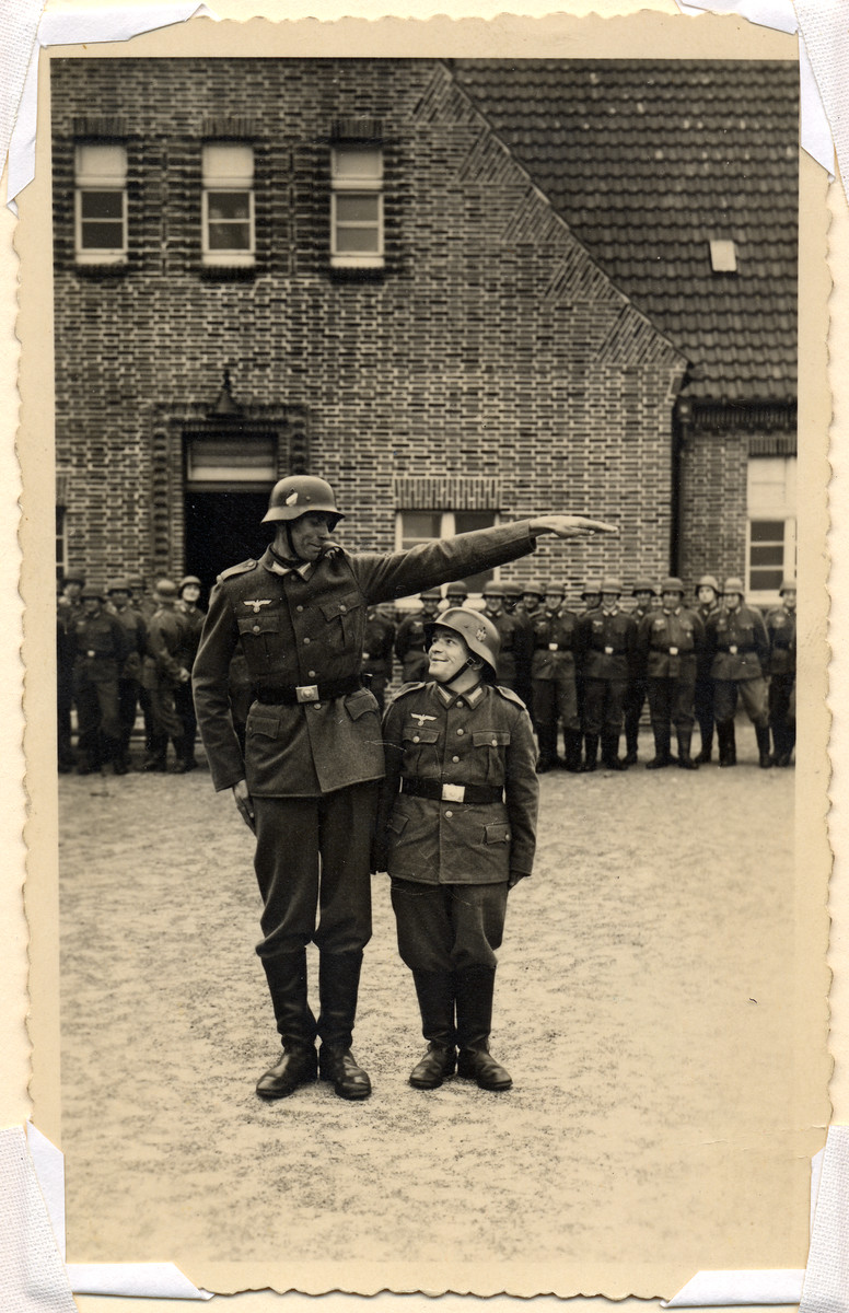 A taller soldier poses next to a smaller one as a joke.