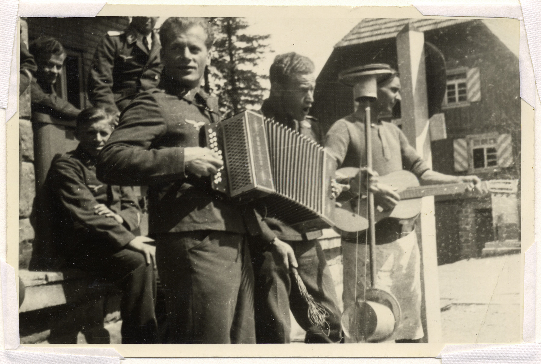A German soldier with an accordian performs together with a guitarist who is not in uniform.