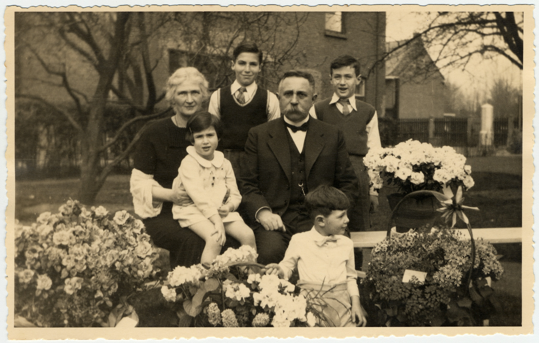The Vromen and Van Dam families celebrate the 60th birthday of Isidoor van Dam.  Pictured are Clara van Dam holding Clary Vromen and Isidoor van Dam with Jaap Vromen.  In the back are two older grandchildren.