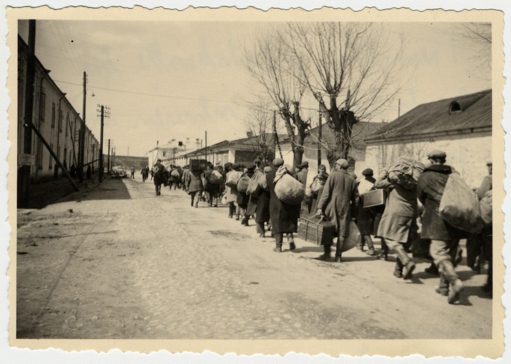 A group of people march down a road with their possessions (probably during either a deportation or relocation action).