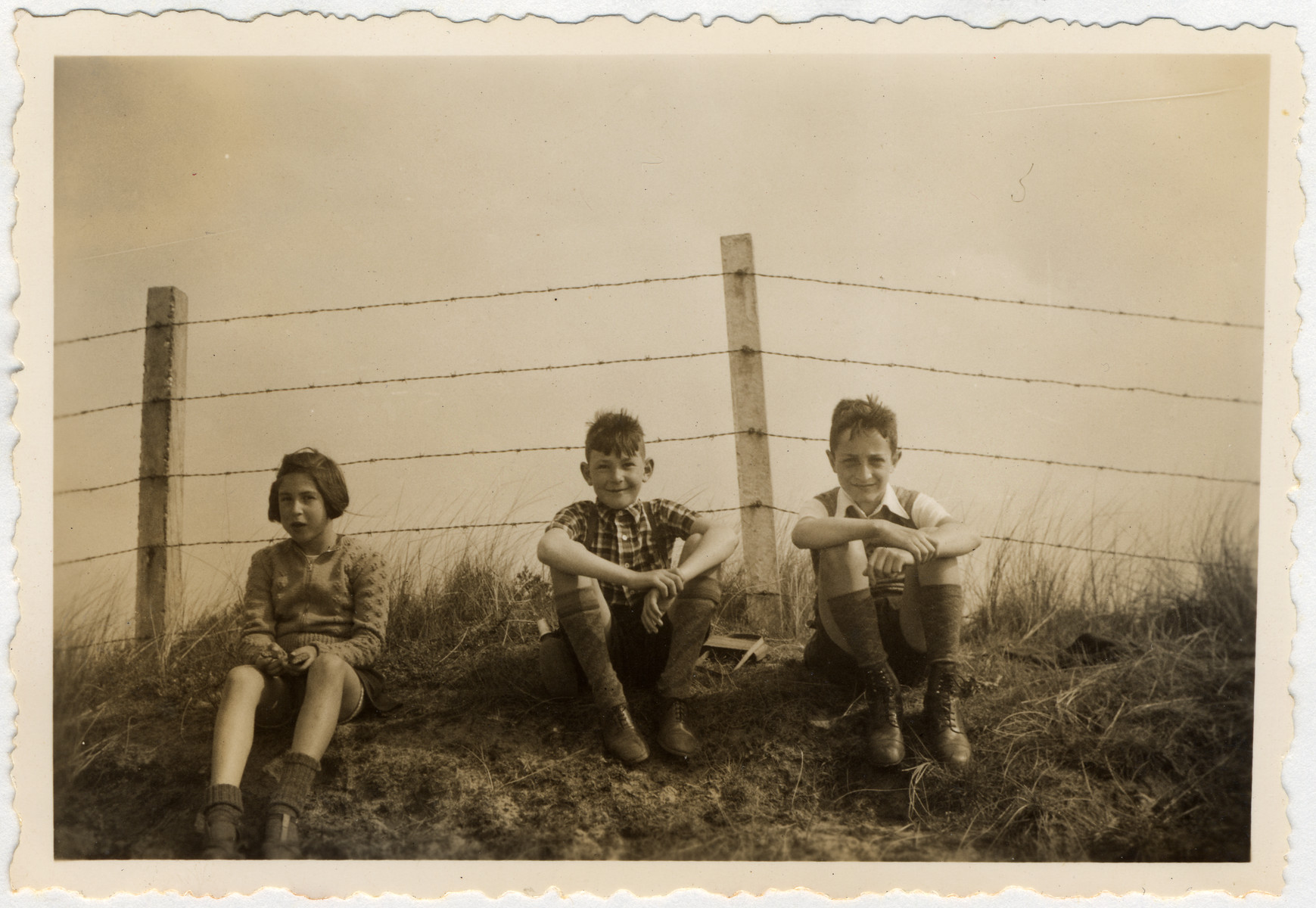 Three children rest during a bike ride to the coast which is blocked off with barbed wire in anticipation of the coming war.  Pictured are Clary and Jaap Vromen and a friend.