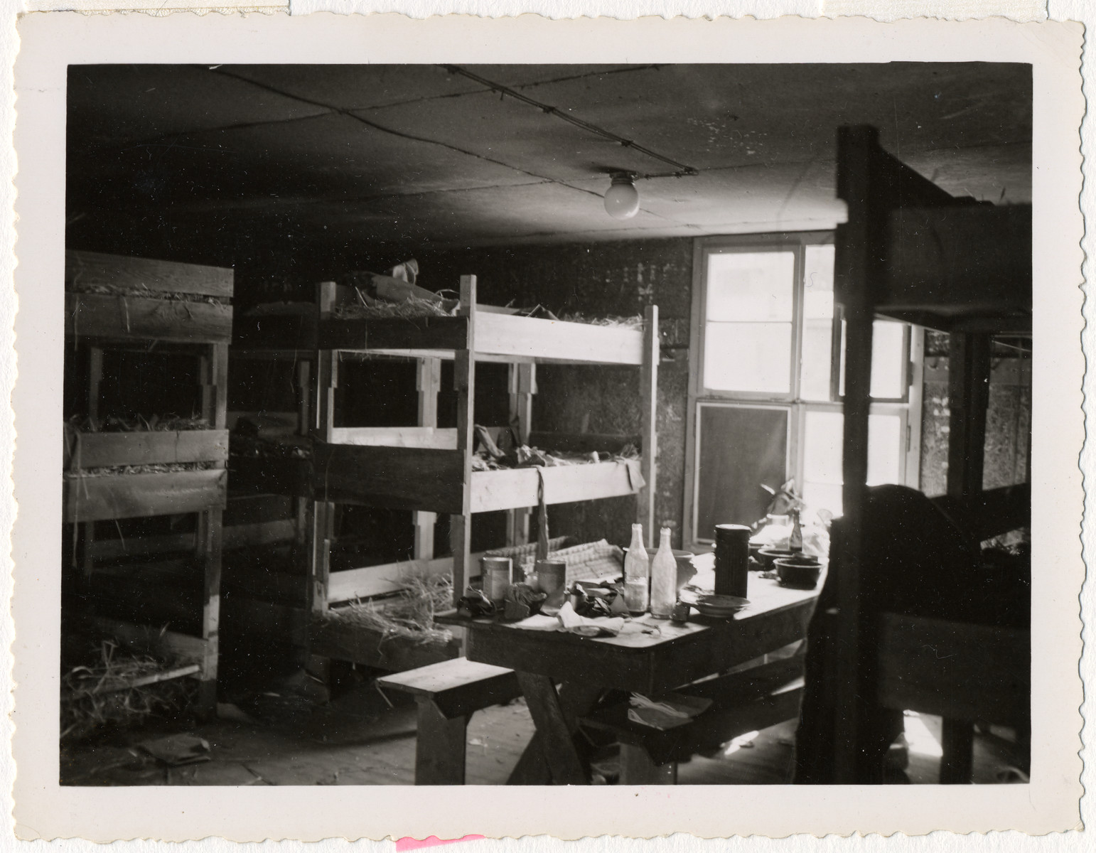 Interior view of the sleeping quarters in a barracks in an unidentified locale.