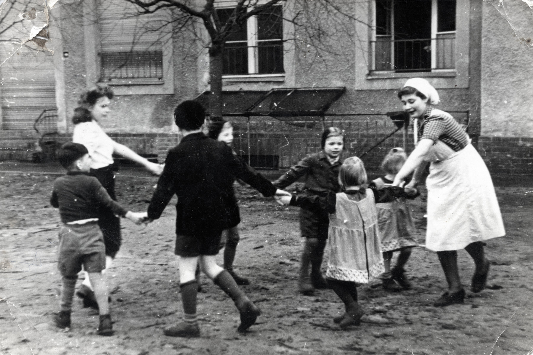 Regina Anders pictured right) plays with children at a day care in postwar Berlin.