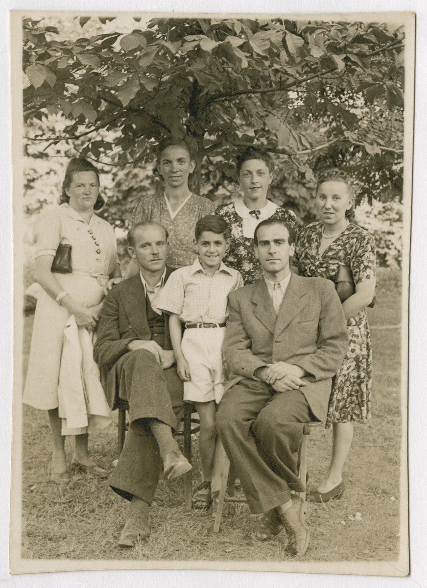Marian Kwasniewski poses with his parents and rescuers after Lwow's liberation.  Marian (standing center), Josef (seated right) and Helena Kwasniewski (standing second from right) pose with their rescuers Janina Mikolajewicz (far left) and Gienia (far right).
