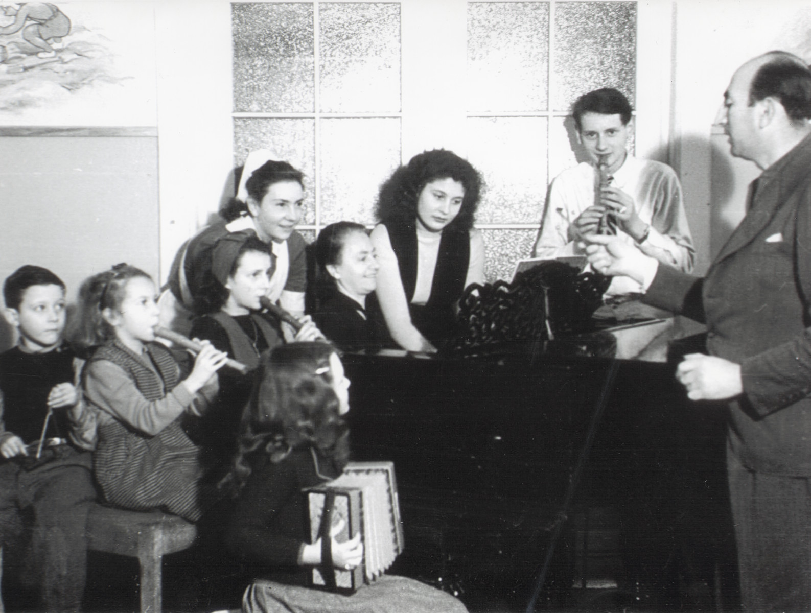 Children play recorder in a music class in Berlin daycare center Niedershoenhausen.   Ruth Anders pictured third from right.  Director of school Seigfried Baruch, pictured right, was in Auschwitz. Wolfgang Rosenthal, second from right. Mrs Scott, pictured fourth from right. Mananne Latter, pictured fifth from right.