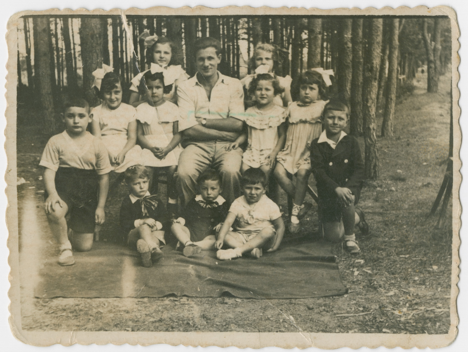 Yehuda Bielski poses with a large group of young children in the woods near Nowogrodek.