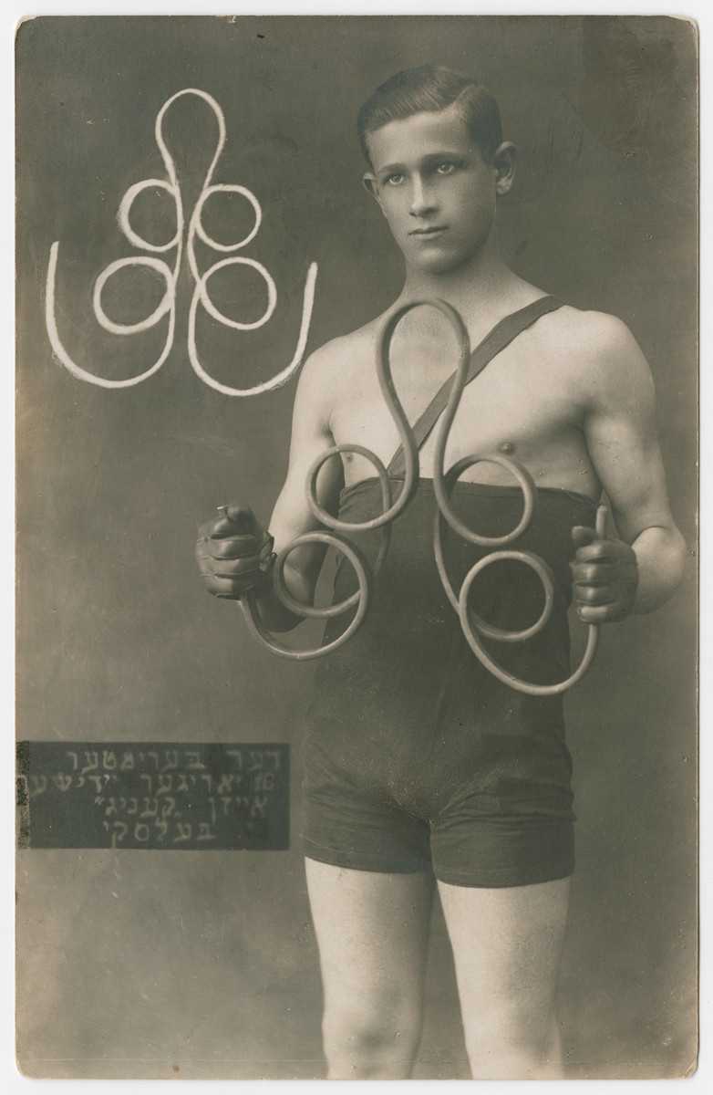 Studio portrait of Yehuda Bielski performing calisthenics with weights.