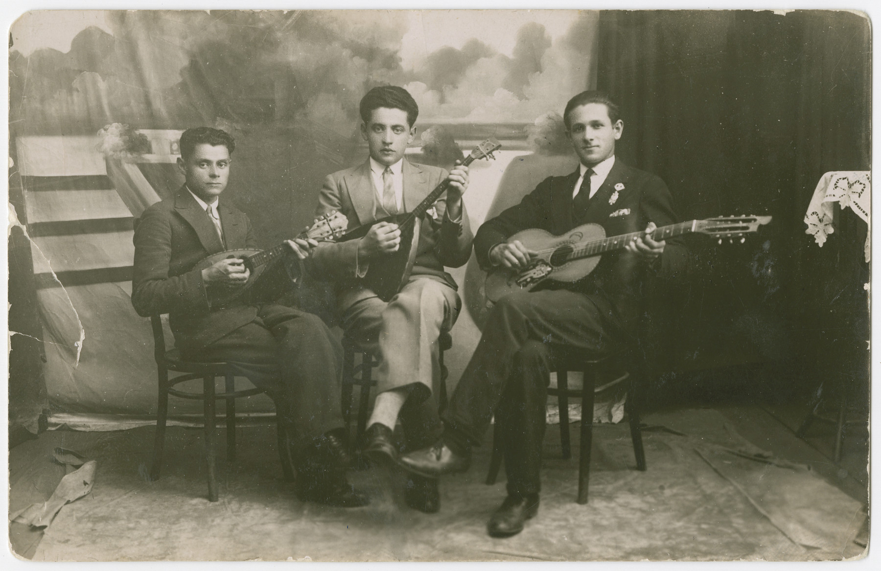 Studio portrait of three Polish Jewish friends playing stringed instruments in an ensemble.  Yehuda Bielski is pictured on the right with a guitar.