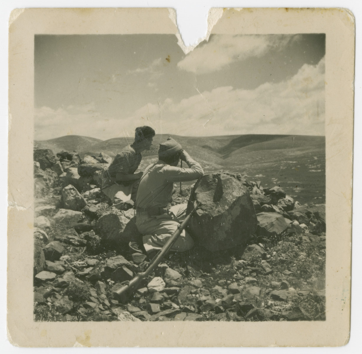 Lt. Yehuda Bielski (left) sits on a rocky hillside and scouts out the situation during the Israeli War of Independence.