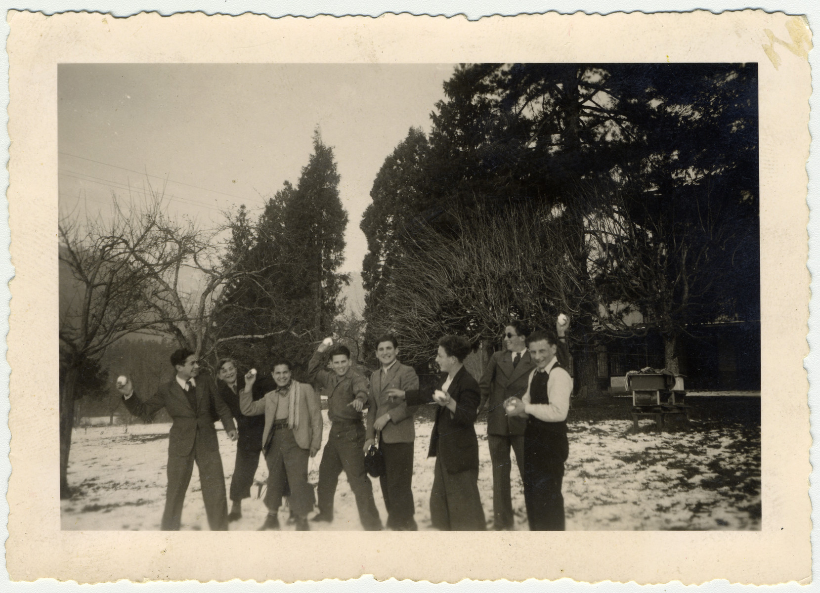"Group portrait of ""Buchenwald Boys"", teenage survivors of Buchenwald, throwing snowballs in a park in Switzerland.  Moniek Schmulewicz is pictured third from the left.  Monek (Murray) Goldfinger is standing second from the right."