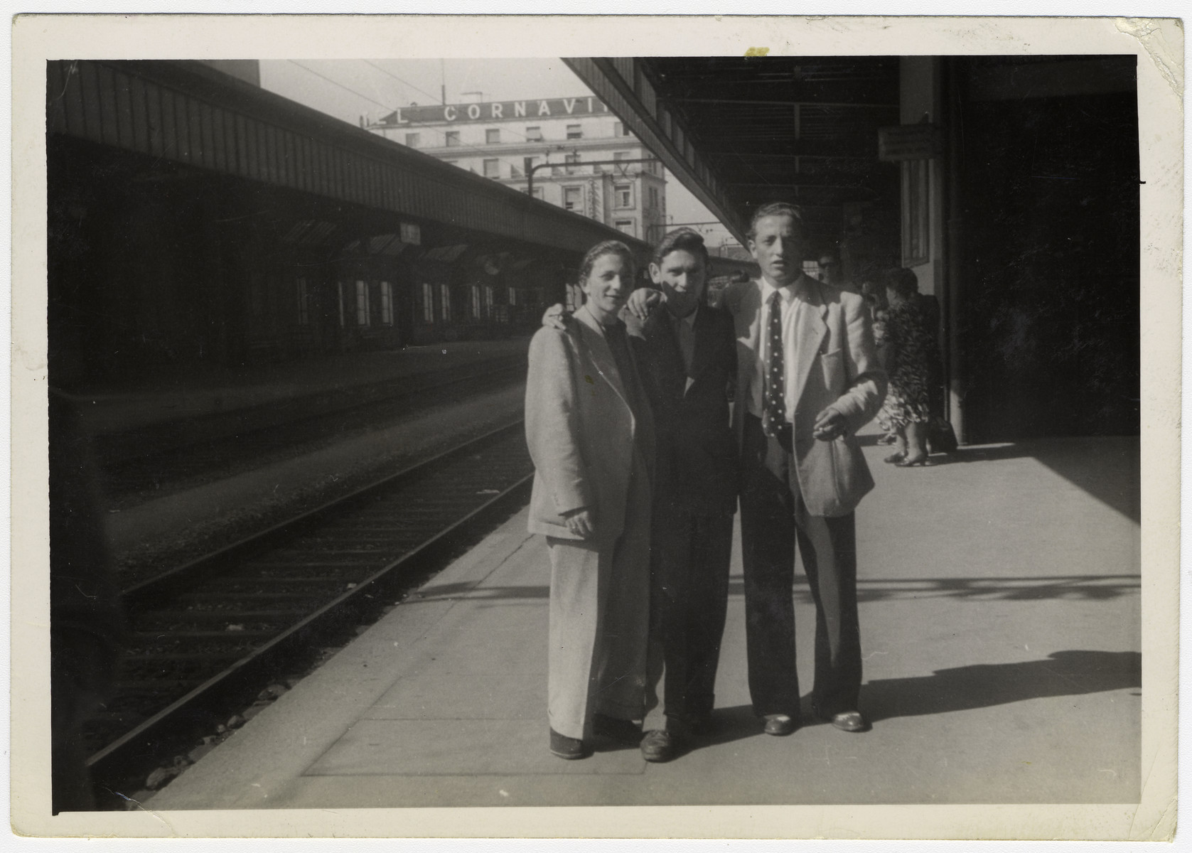 "Three ""Buchenwald Boys"", teenage survivors of Buchenwald, pose on the platform of a train station in Switzerland.  Henry Kolber is pictured on the far left.  Murray (Monek) Goldfinger is on the far right."