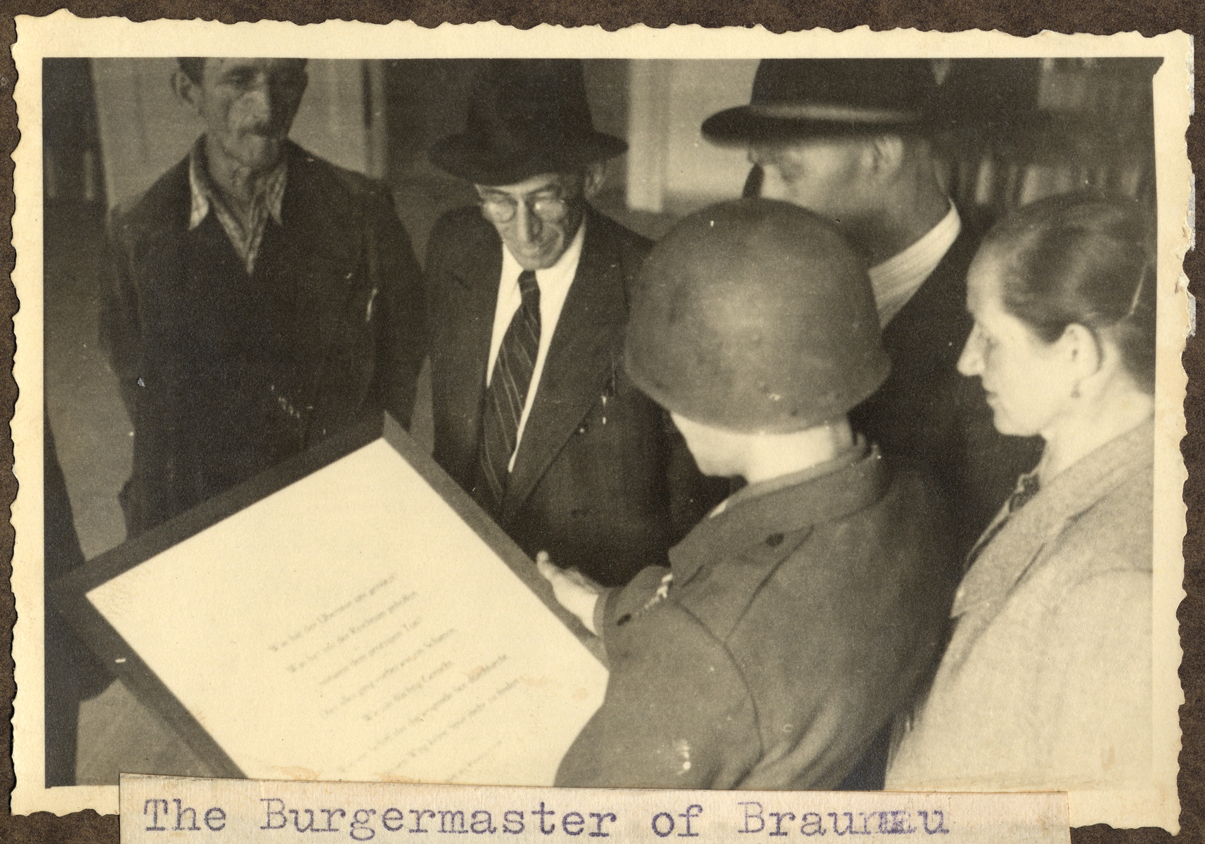 """Joseph Eaton, an American soldier and German-Jewish emigre, sets up a display of biblical quotations in the home where Adolf Hitler was born.  The original caption reads: """"The Burgermaster of Braunau watches the text being hung up."""""""
