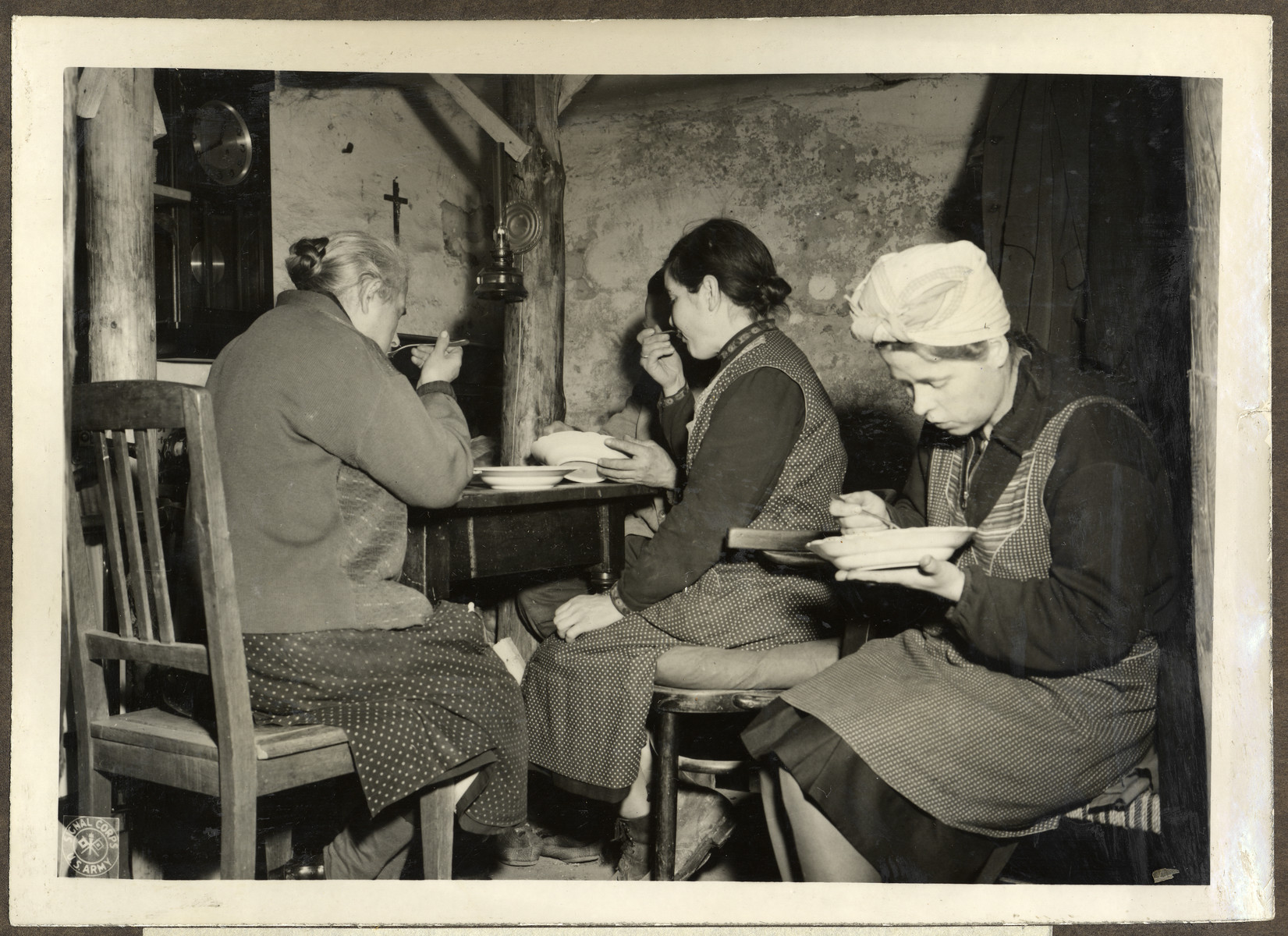 Two German families eat lunch in their bunker in the celler of their destroyed house of Freiedrichsstrasse 15-16, Wurselen. These families lived there for 5 weeks to escape the shelling of their town.
