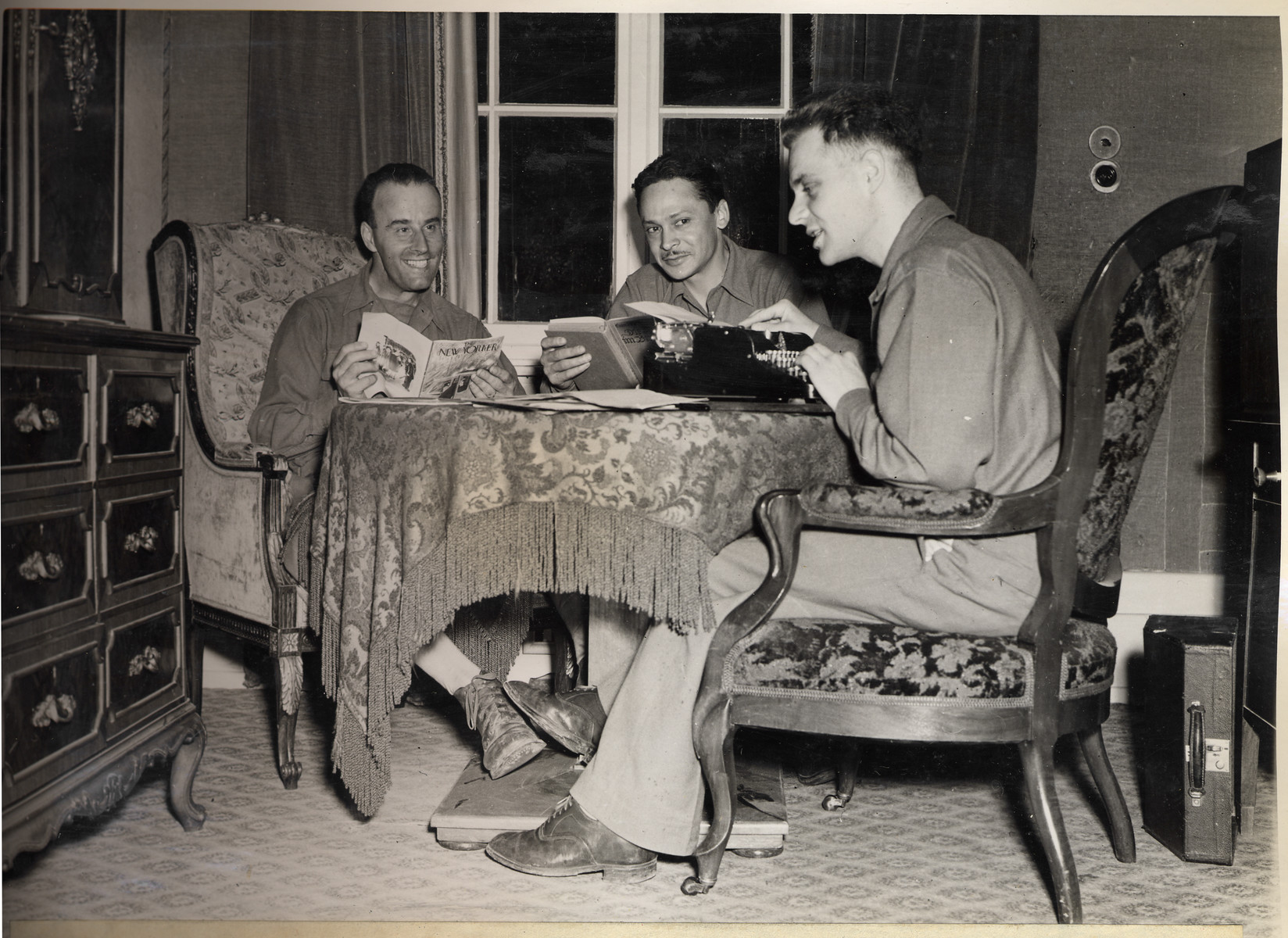 Joseph Eaton, an American soldier assigned to the 4th Communications Unit, types a report in the home that had formerly belonged to an SS doctor.  Also pictured are Dan Oliva and his driver, Hank Blanck.