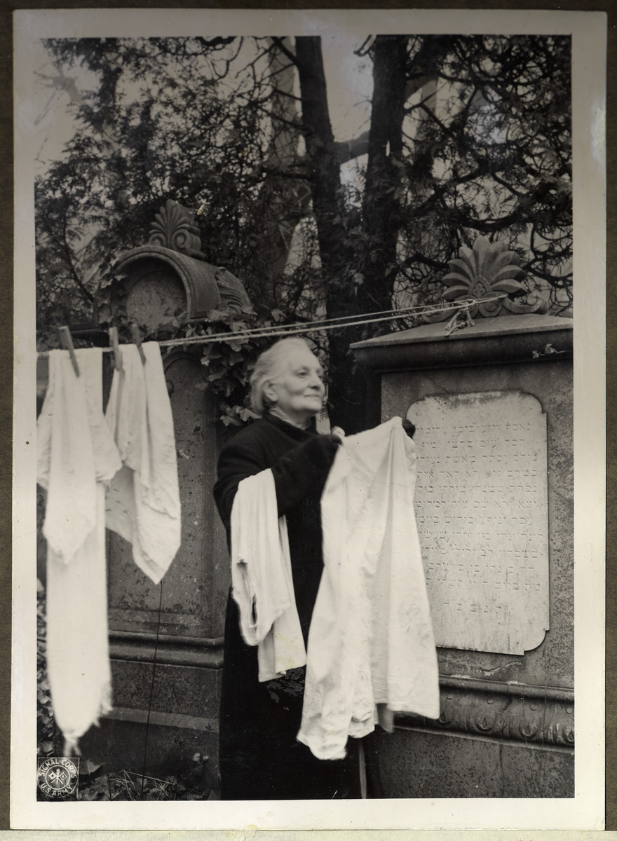 Frau Korbhausen, a German woman who lives in the partly destroyed chapel of the Aachen Jewish cemetary, hangs her laundry to dry among the grave stones.