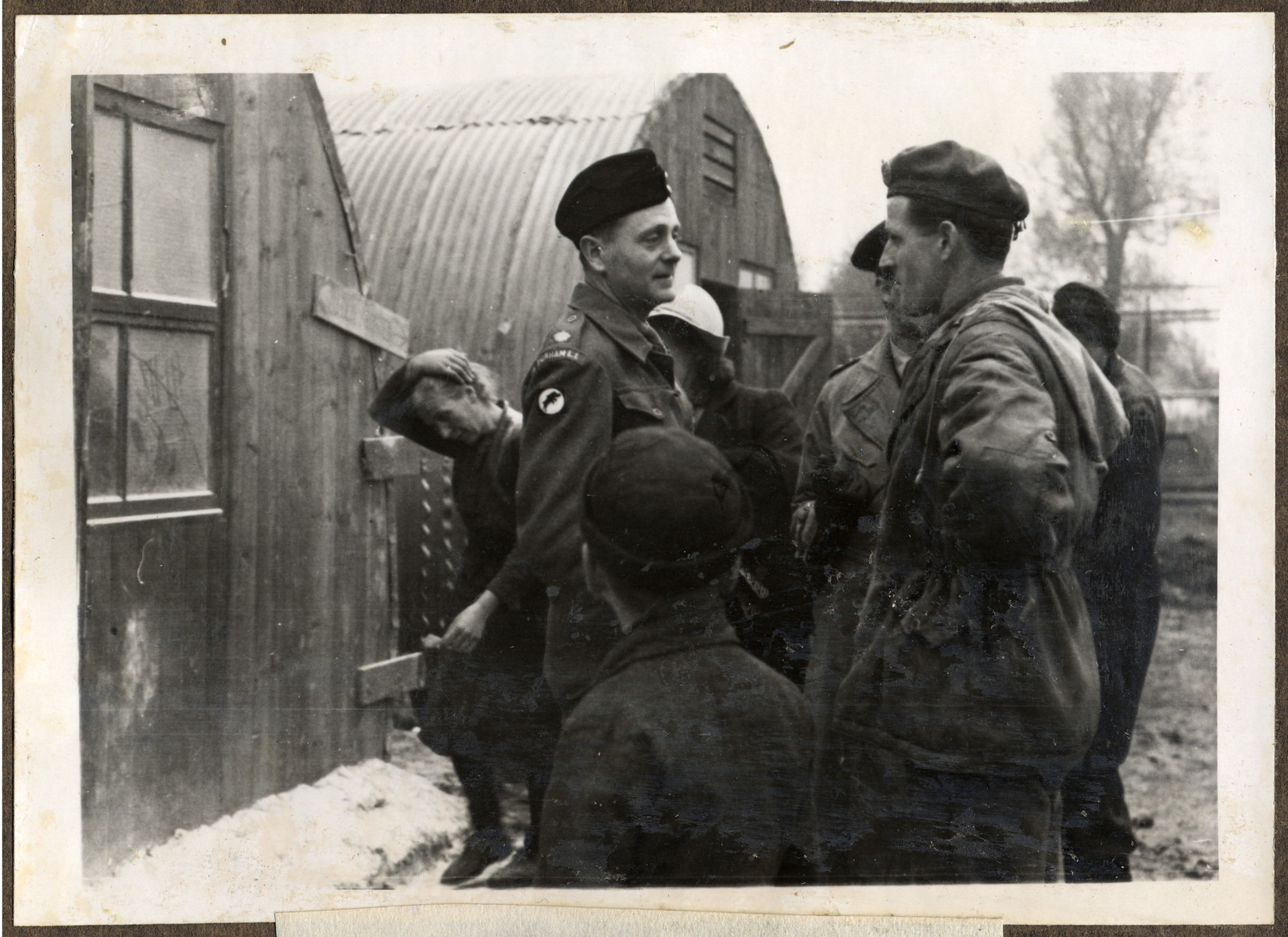 The British commandant of an unidentified British displaced persons' camp talks to another soldier outside a Quonset Hut.