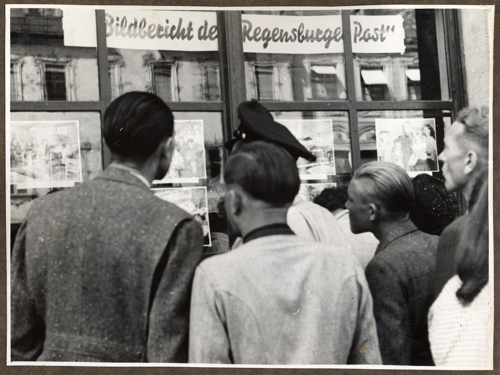German civilians study the weekly photo-news exhibit of the American printed Regenburg Post in Straubing.   The newspaper was edited by the donor, Joseph Eaton.