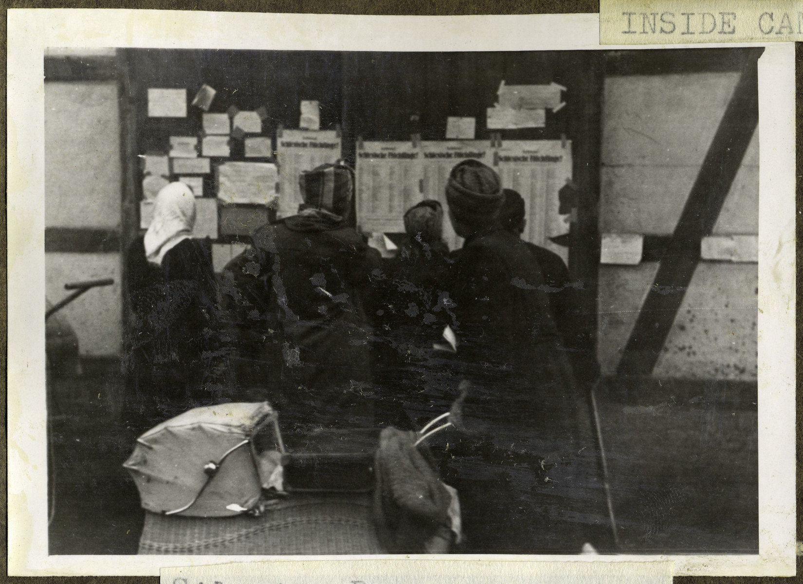Silesian Refugees look at lists for relatives lost during the war.