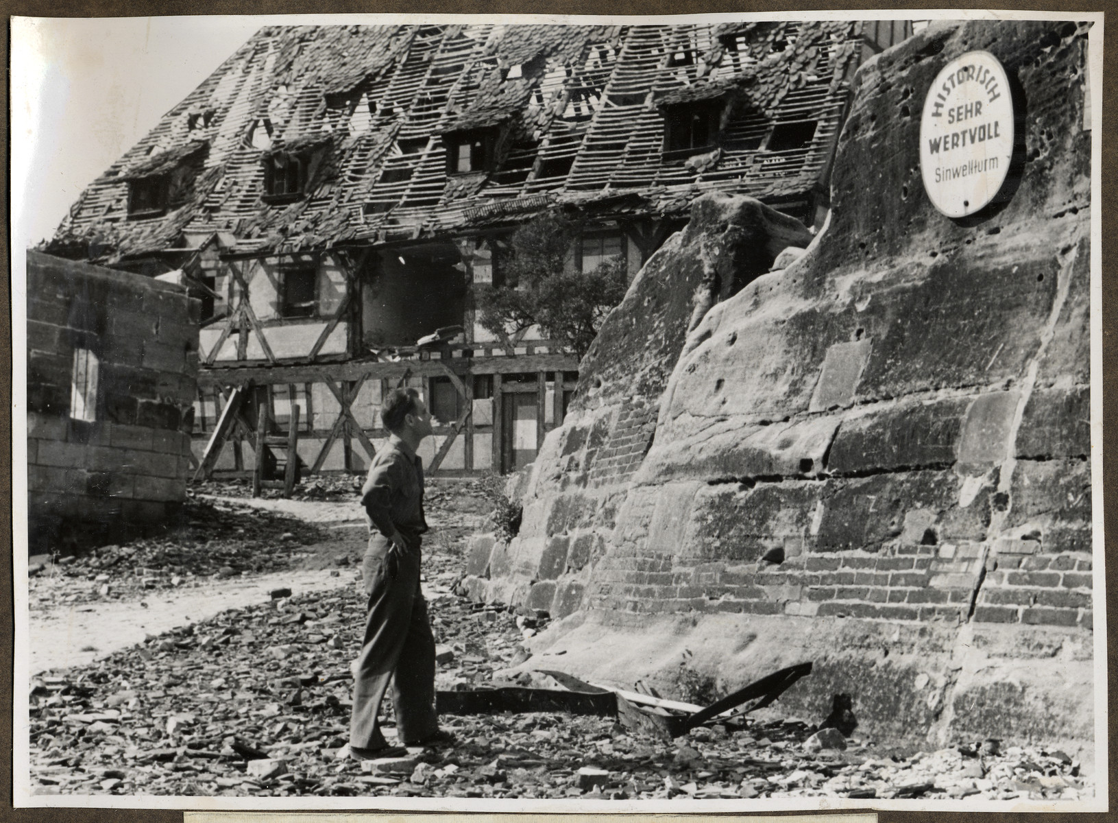 Joseph Eaton, an American soldier and German Jewish emigre inspects a sign on a destroyed building that reads: 'Historically very valuable.'